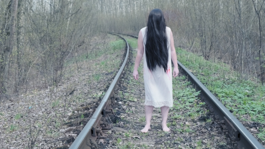 Ghost of woman stands in forest on railway track.   Shutterstock HD Video #1053326678