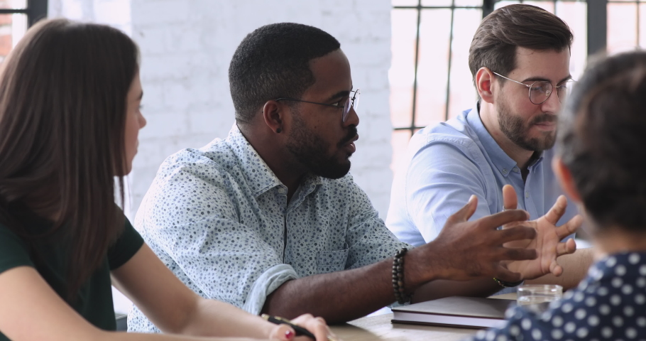 Head shot concentrated african american employee in glasses taking part in project negotiations at brainstorming meeting in office. Group of young mixed race people discussing company growth strategy. Royalty-Free Stock Footage #1053327086