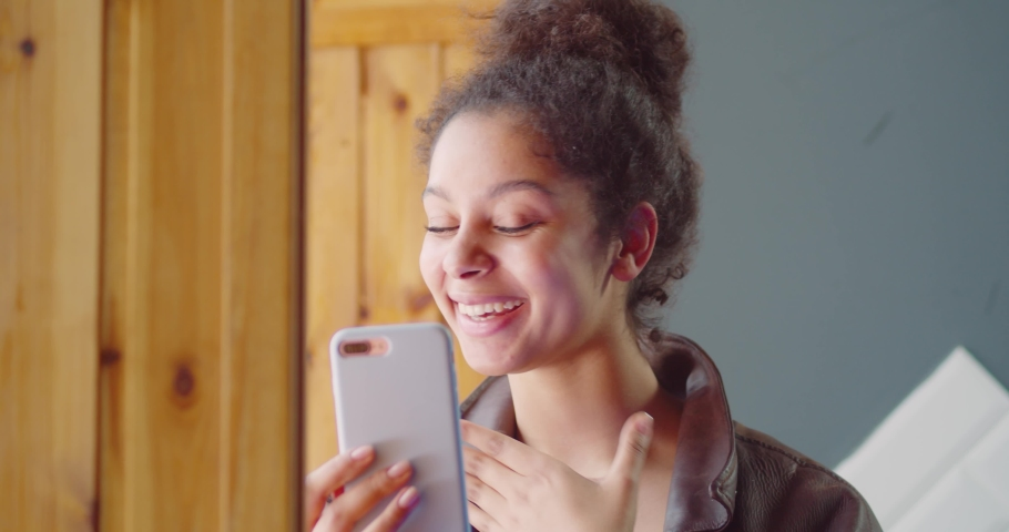 Girl uses cell phone to make a video conference. Online video chat. Selfie. Brazilian woman of mixed race ethnicity wearing colorful purple dress with floral pattern. Summer. Tropical make up.