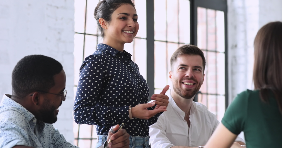 Happy young indian businesswoman standing at table, sharing project ideas with focused mixed race investors at briefing meeting. Professional hindu female mentor coaching millennial colleagues. Royalty-Free Stock Footage #1053327848
