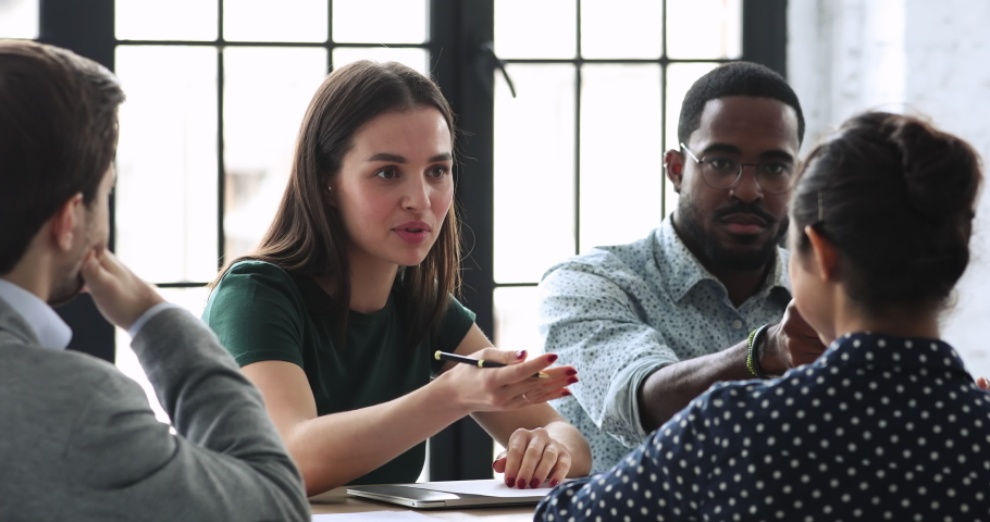 Young female team leader sitting at table with mixed race colleagues, discussing working issues at negotiations meeting. Skilled millennial diverse employees developing startup marketing strategy.