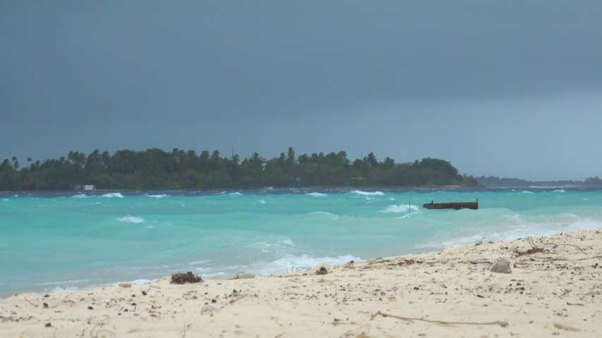 Small wooden boat rocks around in the rough seas with a storm approaching the empty white sand shoreline of Himmafushi. Raging tropical storm approaches a remote island in the Maldives. Rainy season