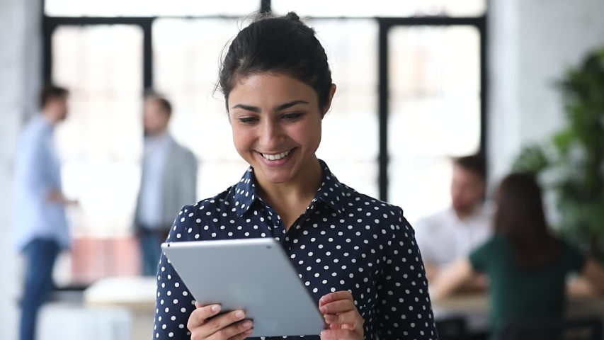 Head shot friendly young indian female manager using digital computer tablet in office. Smart biracial businesswoman working on electronic device, communicating with clients online at workplace. Royalty-Free Stock Footage #1053333521
