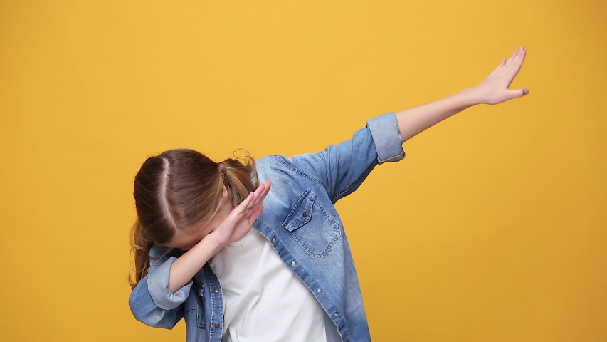Little fun blonde kid teen teenager girl 12-13 years old in denim jacket white t-shirt posing isolated on yellow background studio. People childhood lifestyle concept showing doing DAB dance gesture   Shutterstock HD Video #1053333596