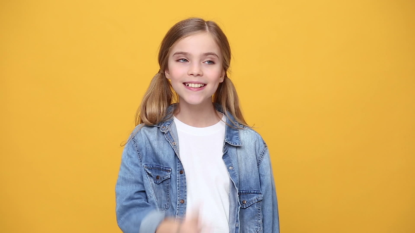 Little kid teen girl 12-13 years old in denim jacket white t-shirt posing saying hush be quiet with finger on lips shhh gesture isolated on yellow background studio. People childhood lifestyle concept   Shutterstock HD Video #1053333632