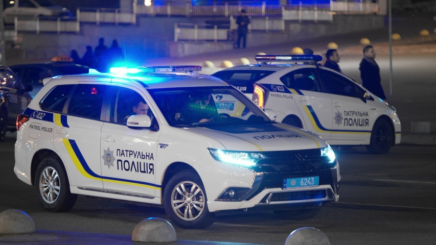 February 29, 2020, Kiev, Ukraine. Two police patrol cars with red and blue flashing lights in the evening on the street among a large number of passers-by. Police officers in a car. Blocked the road.