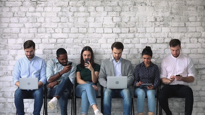 Diverse young people sitting on chairs in row line queue with gadgets, waiting for interesting vacancy job interview. Happy mixed race seekers applicants preparing for meeting with hr manager. Royalty-Free Stock Footage #1053336131