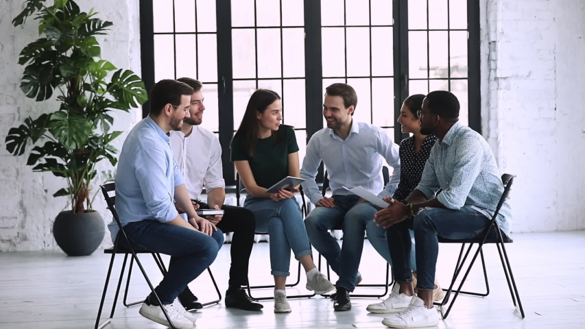 Full length happy young multiracial business people sitting in circle on chairs, chatting in office, slow motion. Smiling diverse millennial coworkers involved in training teambuilding activity. Royalty-Free Stock Footage #1053336194