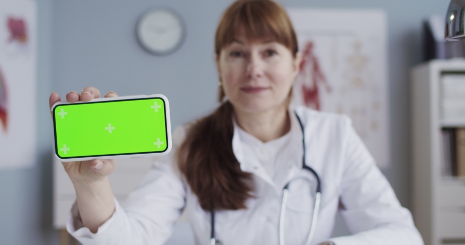 Pretty joyful Caucasian female doctor in white gown holding smartphone with green screen while sitting in cabinet. Beautiful happy physician showing mobile phone with chroma key with tracking motion