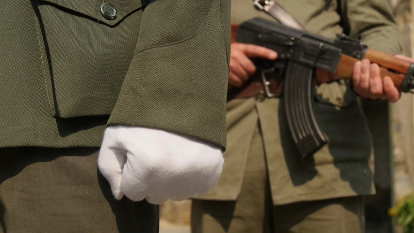 Close-up of a military officer's hand wearing white gloves, clenching his fist as he walks along outdoors followed by an armed guard.