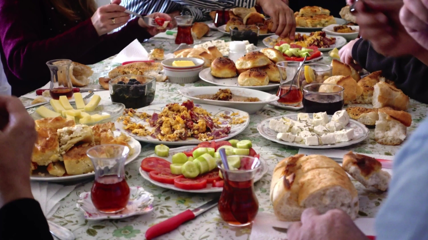 Crowded and hungry Turkish Muslim family having delicious breakfast together (traditional serpme kahvalti) to celebrate Eid-ul-fitr, Feast of Sugar, after the holy month Ramadan