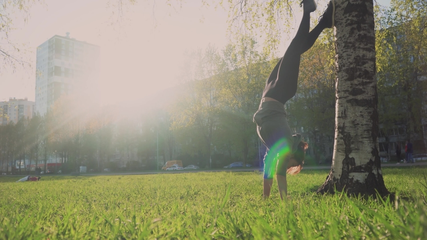 Young athletic girl stood on hands, leaning on a tree in a park on a sunny day, training in the fresh air.