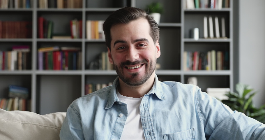 Smiling young handsome man sitting on couch, holding video call, web camera view. Head shot close up happy guy blogger looking at camera, recording educational video, sharing information online. | Shutterstock HD Video #1053347510