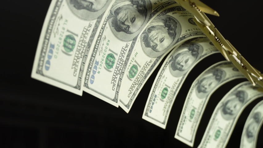 Dollars dry on a clothespin rope. The financial concept of the dollar. Hundred dollar bill on a rope. Money laundering concept. | Shutterstock HD Video #1053348521