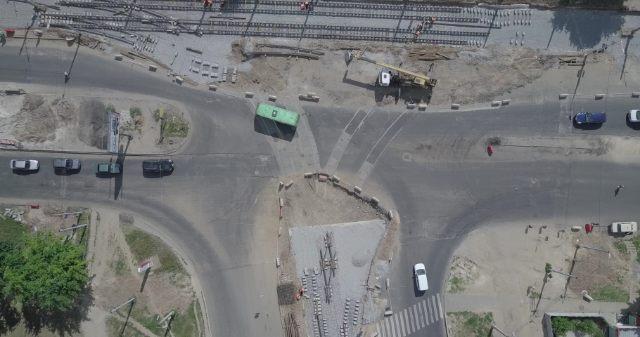 Work crane on the construction of a road. Rails and crushed stone on substrate. Support activities and reconstruction of tram tracks. Aerial view from drone | Shutterstock HD Video #1053350171