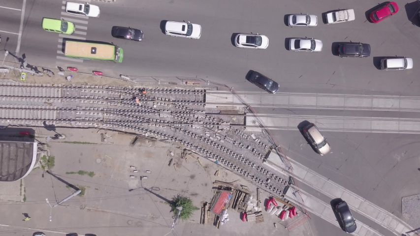 Work machinery on the construction of a road. Traffic on crossroad. Support activities and reconstruction of tram tracks. Aerial top view from drone | Shutterstock HD Video #1053350237