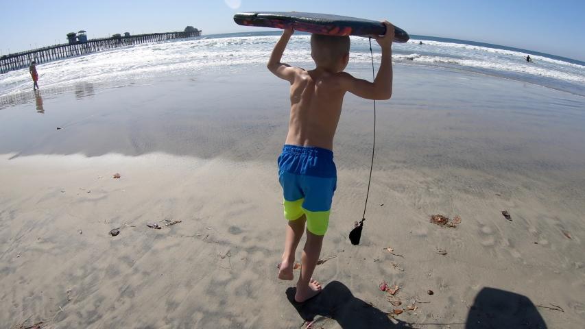 A little boy running into the ocean carrying a boogie board   Shutterstock HD Video #1053350300
