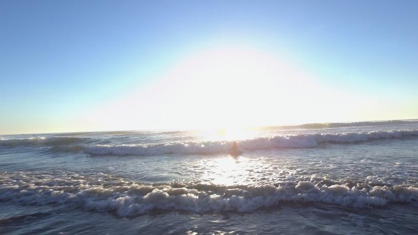 A girl riding a boogie board into shore at beach   Shutterstock HD Video #1053350324