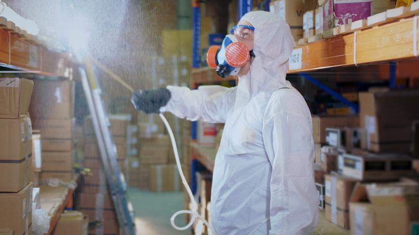 Man Disinfecting Warehouse. Covid-19. Corona Virus Disinfection. Antiseptic Sanitizer. Coronavirus Disinfectant. Worker Wear White Uniform Suit. Protect Mask covid 19. Spray Disinfecter corona virus. Royalty-Free Stock Footage #1053351332