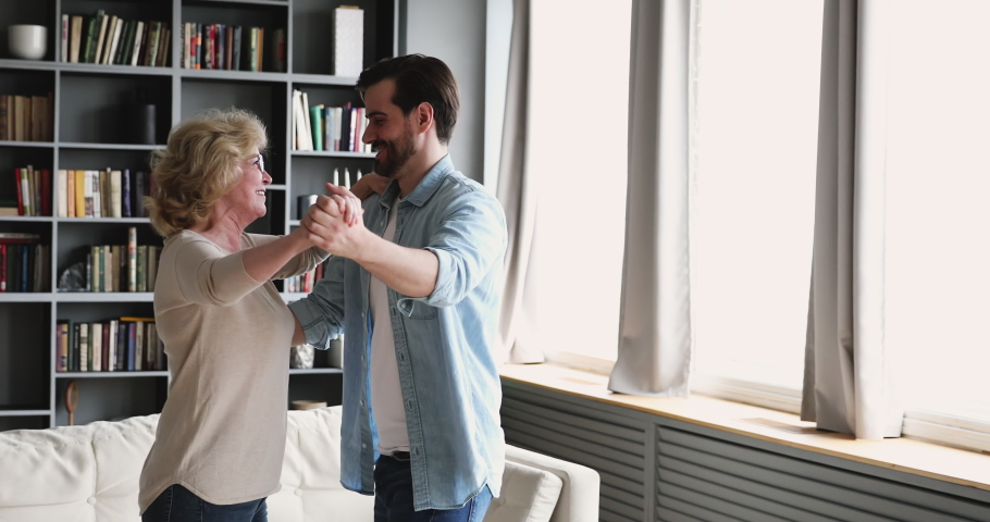 Happy young handsome man dancing waltz with smiling beautiful middle aged mother in living room. Excited senior older woman enjoying moving in pair to favorite slow music with grownup son at home. Royalty-Free Stock Footage #1053352166