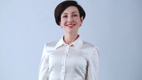 Beautiful young businesswoman posing in studio with friendly smile.Video clip of pretty Caucasian woman in 30s wearing classic formal silk shirt,red lipstick & makeup looking in camera smiling