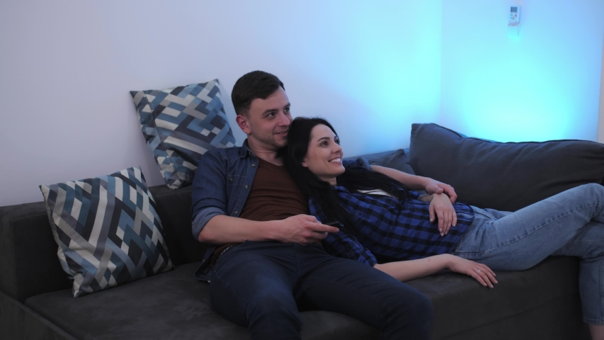 Happy young couple lying, hugging and smiling on sofa in new apartment and watching tv | Shutterstock HD Video #1053359846