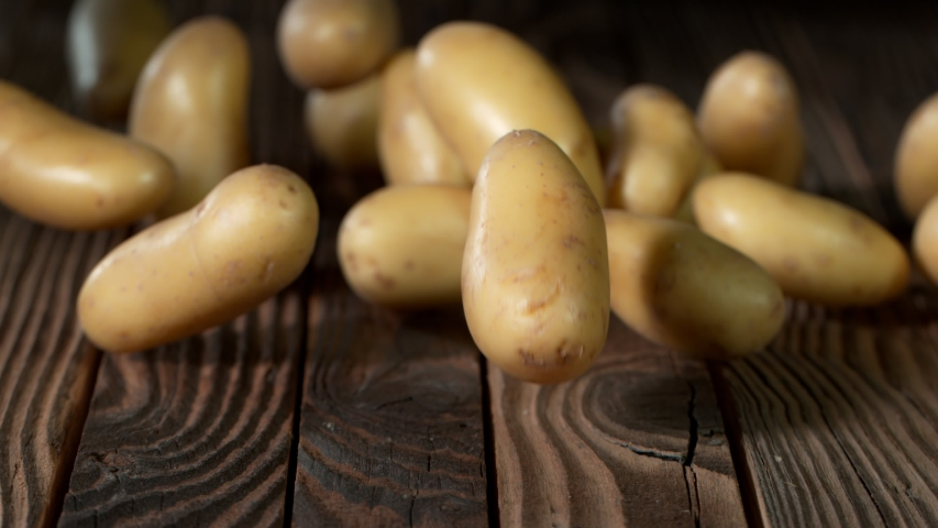 Super Slow Motion Shot of Potatoes Rolling on Old Wooden Table at 1000fps. Royalty-Free Stock Footage #1053362021