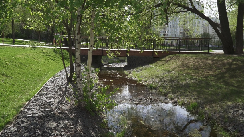 A small creek fortified with stones and a bridge over it in a city park | Shutterstock HD Video #1053363164
