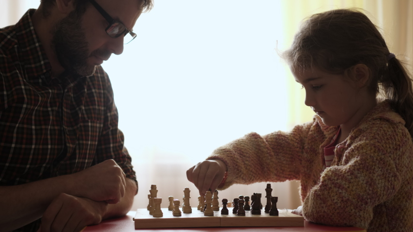 Portrait of Smart Little Girl and Father Playing Chess. Child Playing Chess With Friend at Home, Development of Logical Thinking for Children. Intellect, Intelligence. Development Logical Thinking. | Shutterstock HD Video #1053364304