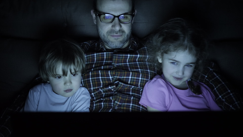 Happy Family While Watching TV on Laptop. Father with Son and Daughter Together Watch Cartoon on Laptop on Living Room. Concept Video Game, Entertainment, Emotions, Family. Children Watching TV.