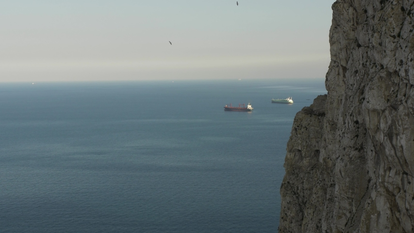 Two oil tankers sail in the distance in Gibraltar's bay. There is a part of Gibraltar's rock visible. | Shutterstock HD Video #1053366014