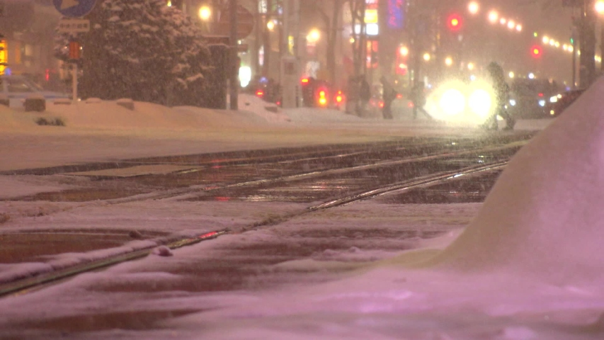 SAPPORO, HOKKAIDO, JAPAN - FEB 2020 : Snow scenery around Susukino city area at night. Soft snow falling at downtown street. Concept of Japanese winter and cold snowing season. Slow motion shot.