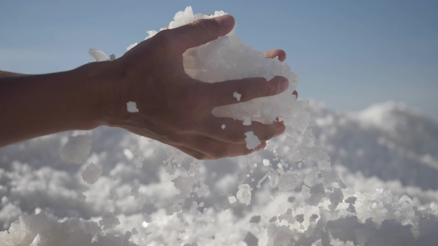 Raw salt crystals in hands. Male hand holding natural salt crystals on the background of a salt lake. White natural salt. natural resources concept, | Shutterstock HD Video #1053369284