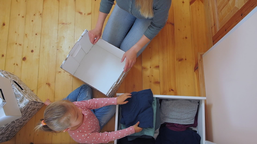 Mother and little daughter putting clothes to card box together. Preparing old clothes to donation Royalty-Free Stock Footage #1053370181