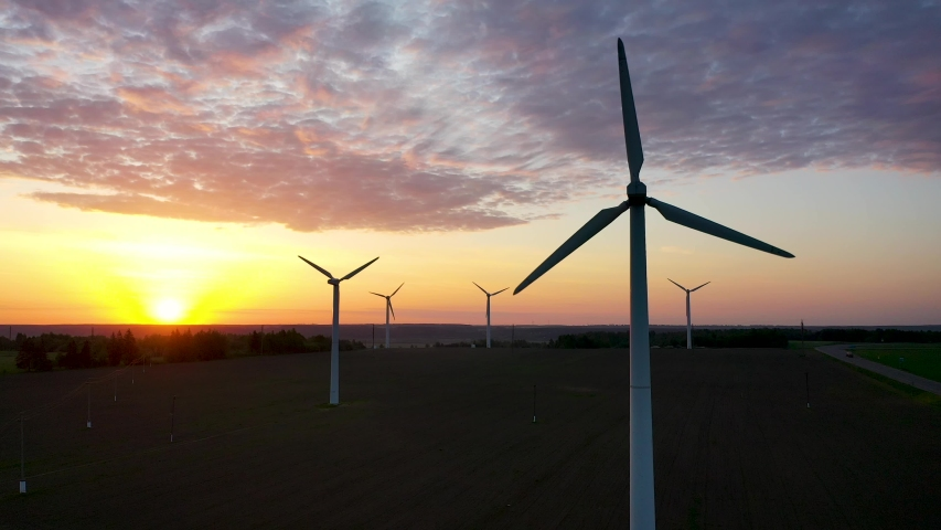 Wind turbine rotate in beautiful purple evening sunset. Renewable energy source production for protect the ecology of our nature world. Aerial view, drone fly up, lot windmills at sunrise | Shutterstock HD Video #1053373103