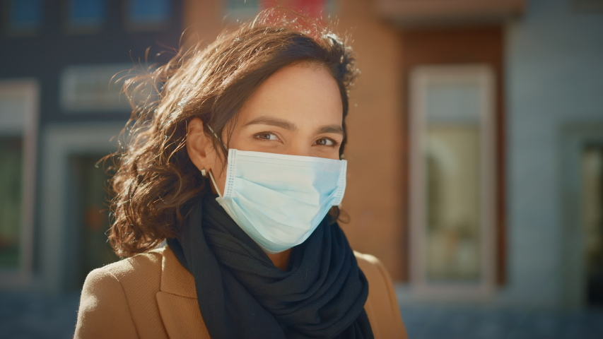 Portrait of a Beautiful Dark Haired Young Woman Wearing Protective Medical Face Mask and Standing on the Street. Safe and Happy Woman Practicing Social Distancing, Quarantine. Blurred City Background Royalty-Free Stock Footage #1053374318
