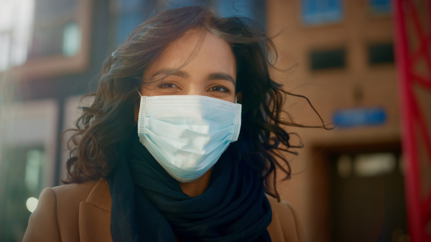 Portrait of a Beautiful Dark Haired Young Woman Wearing Protective Medical Face Mask and Standing on the Street. Safe and Happy Woman Practicing Social Distancing, Quarantine. Blurred City Background Royalty-Free Stock Footage #1053374321