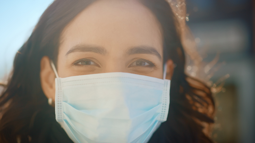 Portrait of a Beautiful Dark Haired Young Woman Wearing Protective Medical Face Mask and Standing on the Street. Safe and Happy Woman Practicing Social Distancing, Quarantine, Air Pollution. Close-up  Royalty-Free Stock Footage #1053374342