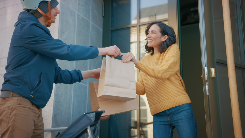 Happy Food Delivery Man Wearing Thermal Backpack on a Bike Delivers Restaurant Order to a Beautiful Female Customer. Courier Delivers Takeaway Lunch to Gorgeous Girl in Modern City Center. Slow Motion Royalty-Free Stock Footage #1053374399