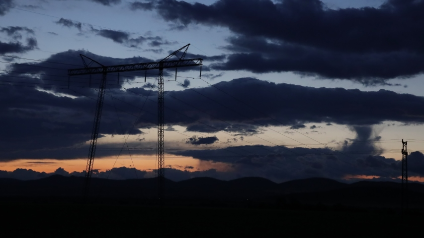 High voltage electric pole under moving clouds at sunset | Shutterstock HD Video #1053374714