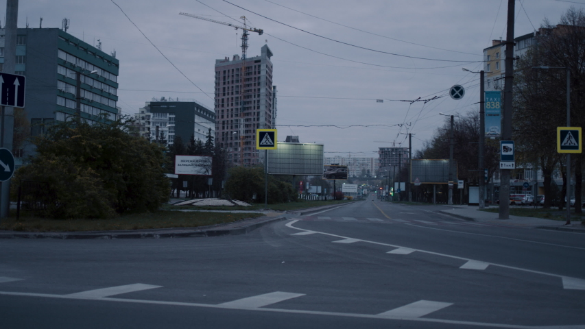 View from car in empty steet in city on cloudy gray morning. Empty streets of town. Car driving at urban road. Stock footage. | Shutterstock HD Video #1053376703