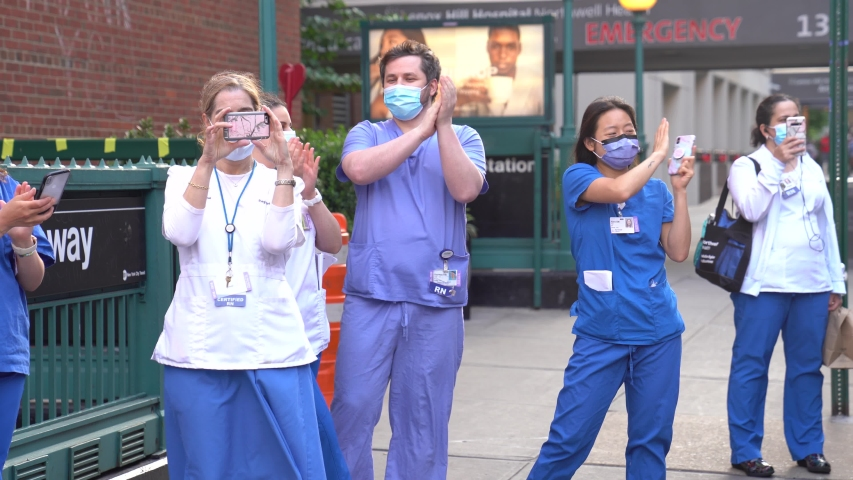 New York City, New York / USA - May 29 2020: New York hospital healthcare workers and nurses clapping expressing gratitude for saving lives during pandemic coronavirus outbreak in New York City.