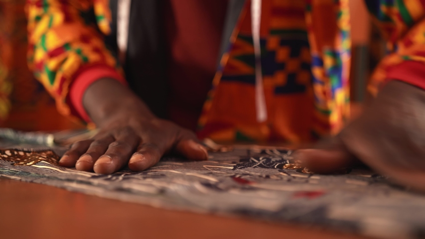 Unrecognizable crop African American tailor in orange jacket cutting blue textile with scissors while working in sewing workshop on daytime | Shutterstock HD Video #1053379847