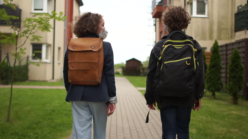 Curly teens, a boy and a girl go to school in protective masks. Back to school after quarantine, ending the lockdown. Rear view. Post-Quarantine Life Royalty-Free Stock Footage #1053383768