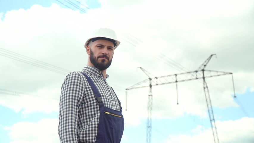 Portrait of engineer near transmission lines. Energy efficiency conception. Transmission towers | Shutterstock HD Video #1053388589