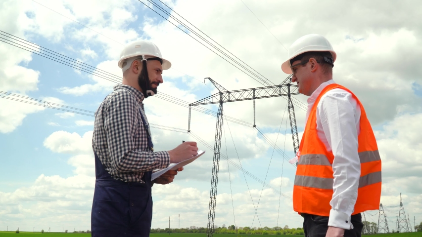 Two engineers working near transmission lines. Manager gives task to subordinate near transmission lines. Electricity pylons | Shutterstock HD Video #1053388601