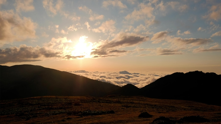 Beautiful nature sunset in georgian mountains Kazbegi. Moving clouds from the horizon. Sun is goes down. View from above to the amazing valley. Sun llights in the haze. | Shutterstock HD Video #1053391928