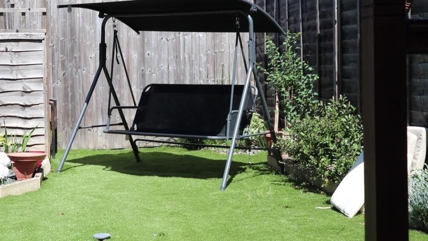 Double garden swing placed in the lush garden in summer  | Shutterstock HD Video #1053392678