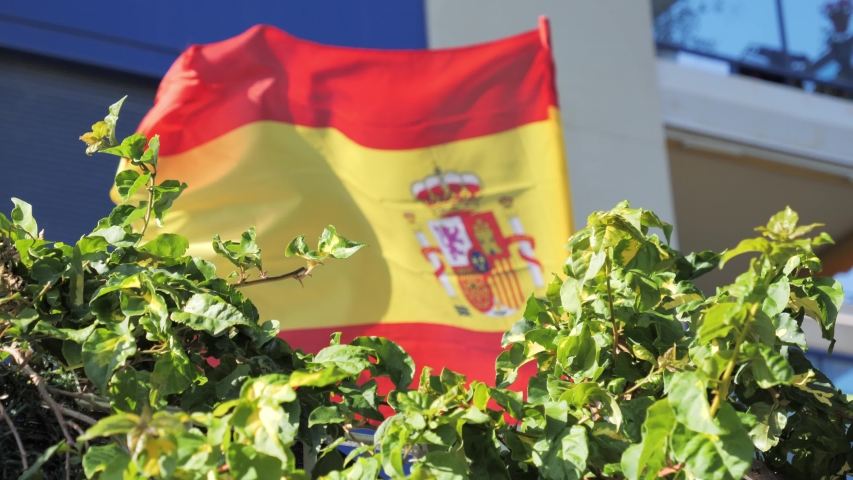 Spanish flag waving by the wind near residential apartment building in Spain | Shutterstock HD Video #1053394118