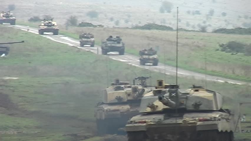 Military tanks driving along a road. Handheld shot. Shot in letterboxed 16:9